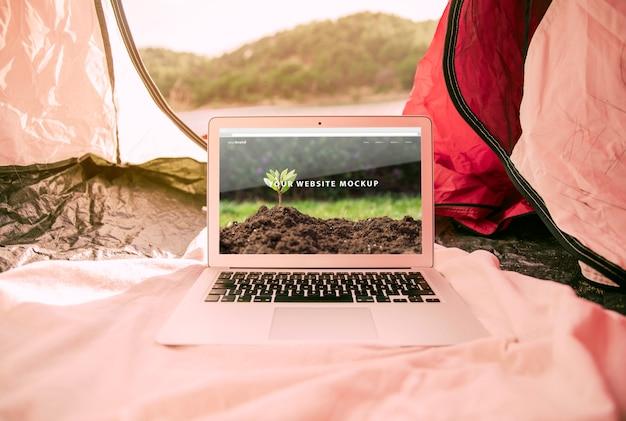 Laptopmodell mit dem kampieren im naturkonzept