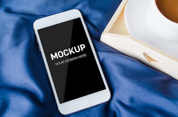Leerer smartphonebildschirm und tasse kaffee auf einem tablett auf dem bett