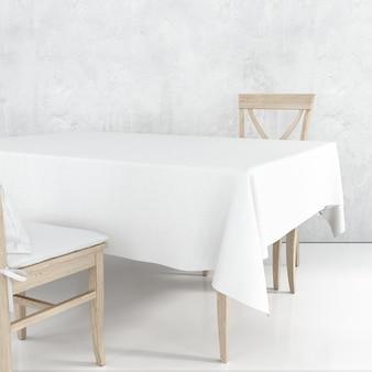 Leeres esstischmodell mit weißem stoff und holzstühlen