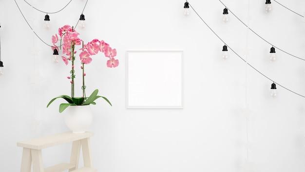Leeres fotorahmenmodell mit lampen, die an weißer wand und schöner dekorativer rosa blume hängen