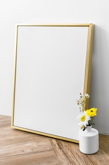Leeres goldenes rahmenmodell durch eine vase mit blumen