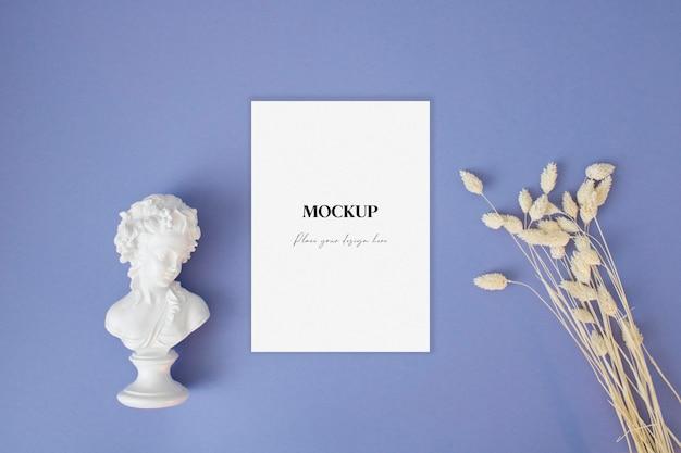 Leeres grußkartenmodell mit trockenem gras und statue auf blauem hintergrund