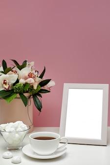 Leeres modell der vorderansicht des fotorahmens auf dem rosa tisch. orchideenblüten, eine tasse tee und süßigkeiten.