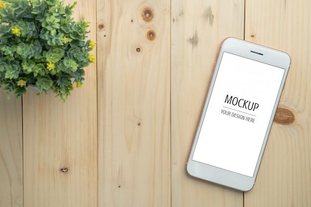 Leeres smartphonemodell des weißen schirmes auf hölzernem tabellen- und kopienraumhintergrund