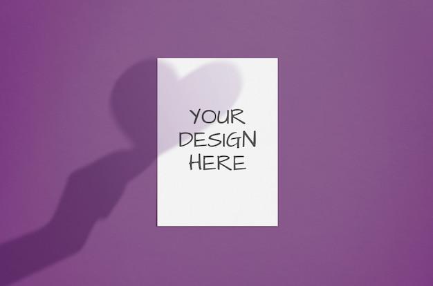 Leeres weißes vertikales papier mit hand- und herzschattenüberlagerung. moderner und stilvoller valentinsgrußgrußkarten- oder -hochzeitseinladungsspott oben
