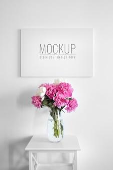Leinwandmodell an weißer wand und vase mit rosa blumen