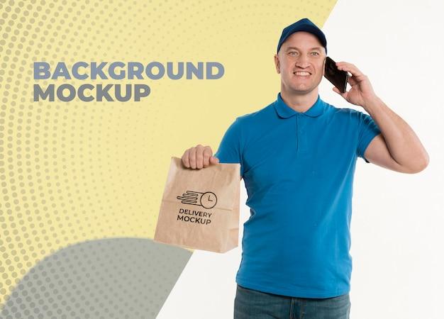Lieferbote, der eine einkaufstasche hält, während er am telefon spricht