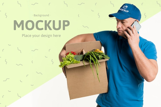 Lieferbote hält eine kiste voll mit gemüse, während er am telefon spricht
