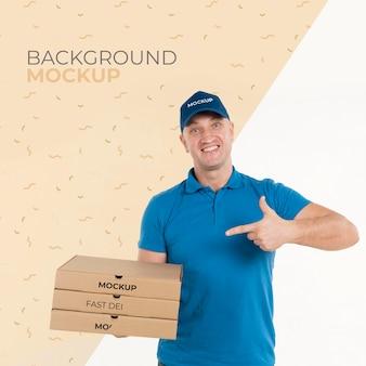 Lieferbote hält einen haufen pizzaschachteln
