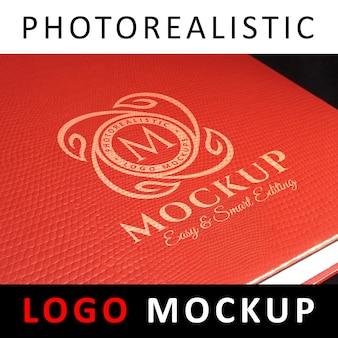Logo mock up - weißes logo auf rotem bucheinband aus leder gedruckt