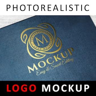 Logo mockup - goldfolie, die auf blauer strukturierter abdeckung stempelt