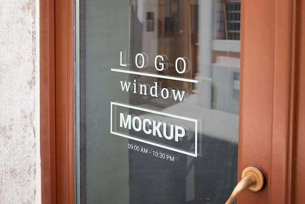 Logo-modell auf dem haustürfenster des geschäfts