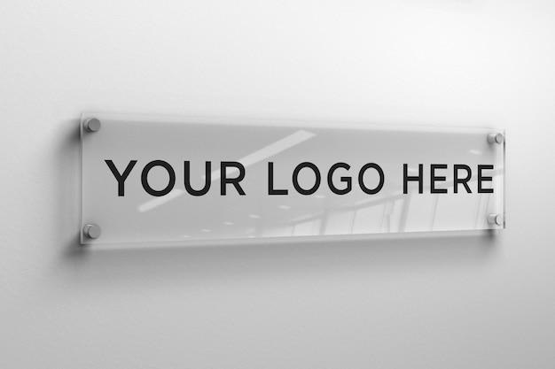 Logo-modell auf einer rechteckigen glasplatte an der wand