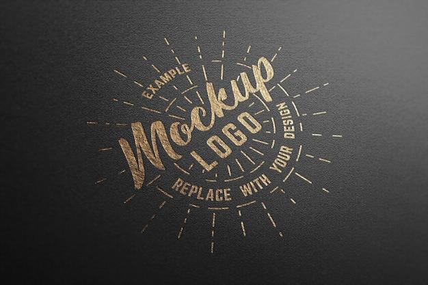 Logo-modell auf schwarzem papier mit goldeffekt