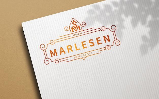 Logo-modell auf weißem bastelpapier mit geprägtem effekt