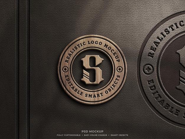 Logomodell aus holz und leder auf braunem leder gepresst
