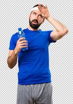 Lustiger sportler mit einer flasche wasser