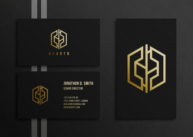 Luxuriöses goldenes logo und visitenkartenmodell auf schwarzer oberfläche