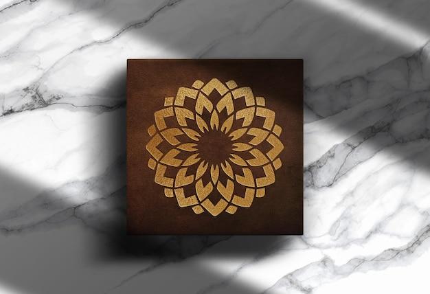 Luxuriöses goldgeprägtes logo aus leder mit quadratischem kastenmodell mit marmorhintergrund
