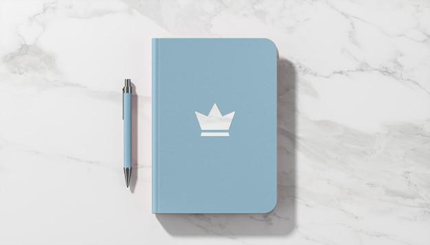 Luxuriöses logo-modell auf weißer marmorfliese des blauen tagebuchs