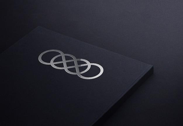 Luxuriöses silbernes logo-modell auf visitenkarte des schwarzen notizblockbuchs