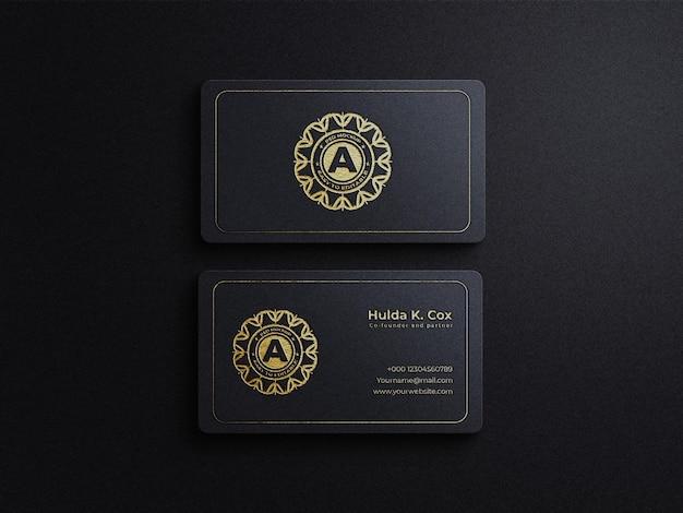 Luxuriöses visitenkartenmodell aus goldener folie auf schwarzem kraftpapier