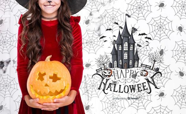 Mädchen, das einen geschnitzten kürbis für halloween-party anhält