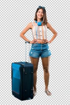 Mädchen, das mit ihrem koffer aufwirft mit den armen an der hüfte reist