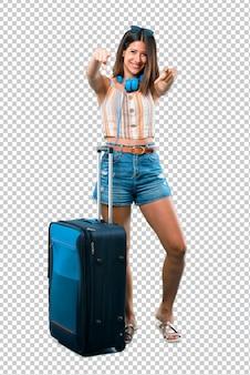 Mädchen, das mit ihrem koffer mit dem finger auf jemand reist und viel lacht
