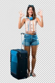 Mädchen, das mit ihrem koffer reist, der ein okayzeichen mit den fingern zeigt. gesicht des glücks und der zufriedenheit