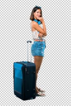 Mädchen, das mit ihrem koffer viel lächelt, während hände auf kasten gesetzt werden