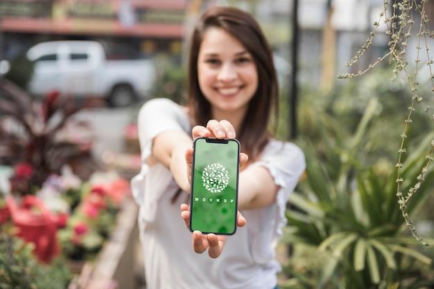 Mädchen, das smartphonemodell mit gartenarbeitkonzept hält
