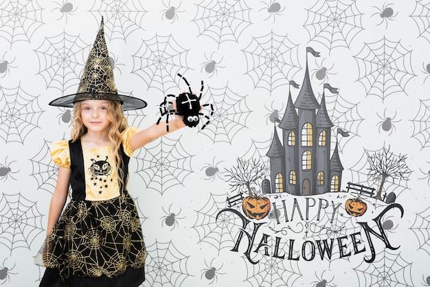 Mädchen gekleidet als hexe, die eine spinne zeigt