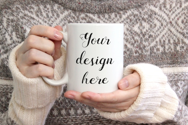 Mädchen im kuscheligen pullover hält weiße keramikkaffeetasse, modell