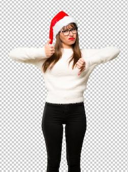 Mädchen mit dem feiern der weihnachtsfeiertage, die gut-schlechtes zeichen machen. unentschieden zwischen ja oder nein