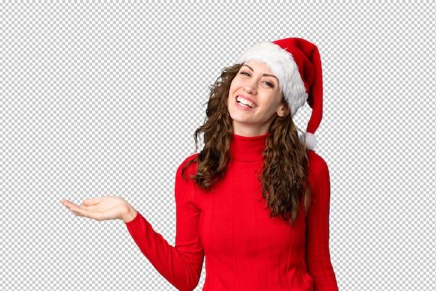 Mädchen mit dem weihnachtshut, der copyspace eingebildet auf der palme hält