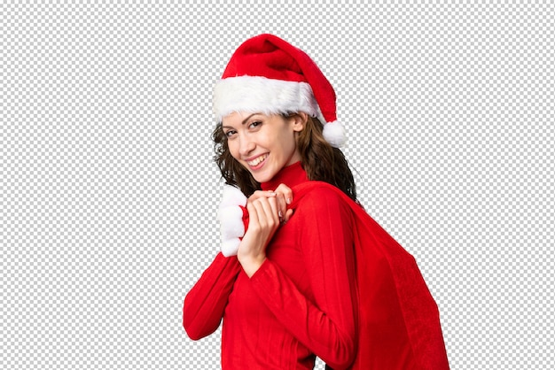 Mädchen mit dem weihnachtshut, der eine weihnachtstasche voll von den geschenken hält
