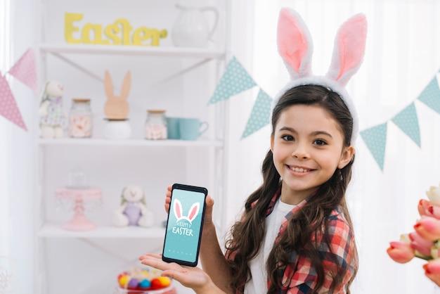 Mädchen mit smartphonemodell an ostern-tag