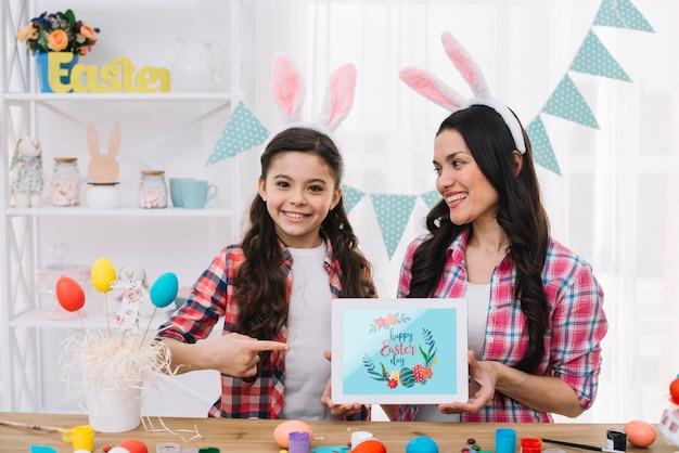Mädchen und mutter mit tablettenmodell an ostern-tag