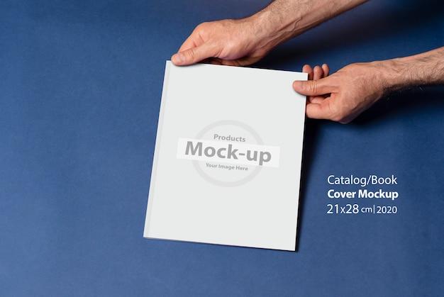 Männliche hände halten einen geschlossenen katalog oder eine zeitschrift mit leerem umschlag