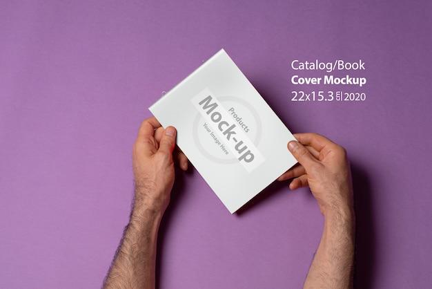 Männliche hände halten einen kleinen a5-katalog mit leerem umschlag auf lila wand
