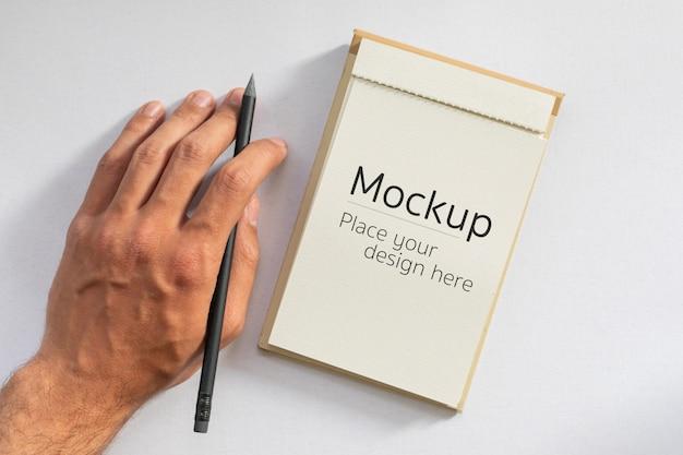 Männliche linke hand, die schwarzen stift neben leerer karte vom notizbuch zum schreiben hält