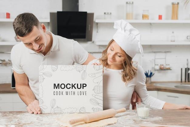 Männliche und weibliche köche halten leeres plakat in der küche