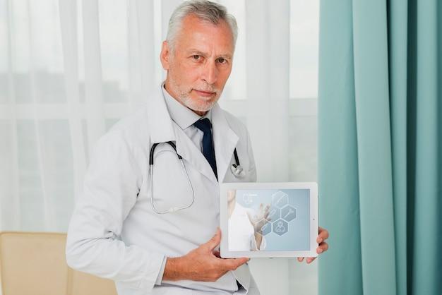 Männlicher doktor, der eine tablette hält