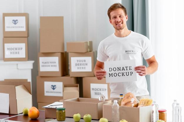 Männlicher freiwilliger, der leeres papier mit nahrungsmittelboxen für spende hält