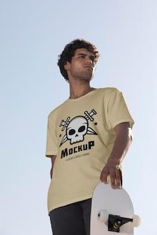 Männlicher skateboarder mit mock-up-t-shirt