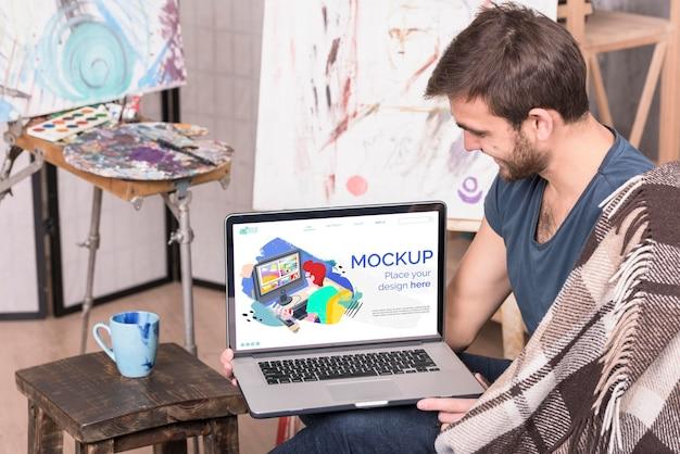 Maler, der ein digitales modell des laptops hält