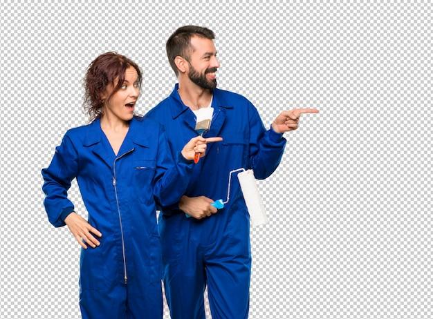 Maler, die finger auf die seite zeigen und ein produkt beim lächeln darstellen
