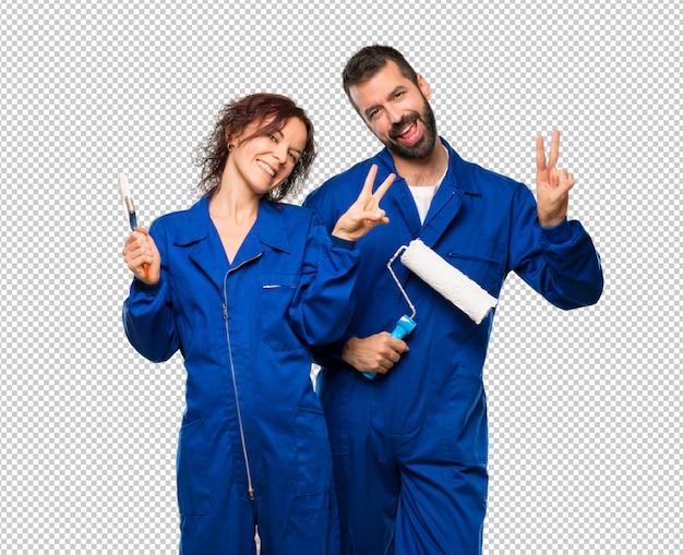 Maler, die victory-zeichen mit beiden händen lächeln und zeigen