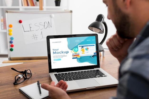 Mann am schreibtisch mit laptop-modell